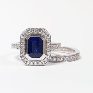 Emerald Cut Ceylon Sapphire in a Grain Set Halo Design Ring with Mill Grain Detail