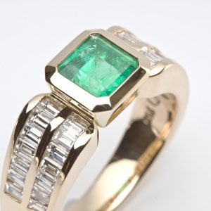 Emerald cut Emerald Bezel Set in a Yellow Gold Ring with Baguette Diamond Shoulders