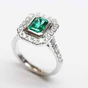 Colombian Emerald Bezel Set in a White Gold and Diamond Halo Design Ring
