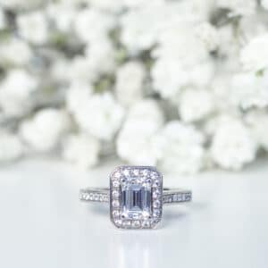 Emerald Cut Diamond in Grain Set Halo Design with Diamond Shoulders