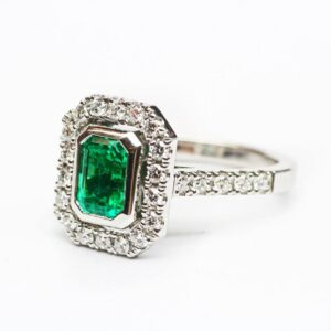 Bezel Set Emerald in a Diamond Halo Design White Gold Ring