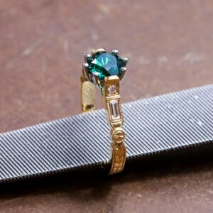 Round Cut Emerald Set in Yellow Gold with Baguette Diamonds and Hand Engraving