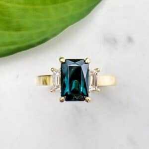 Radiant Cut Teal Sapphire and Baguette Diamond Three Stone Ring