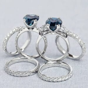 Pair of teal sapphire engagement rings with matching diamond wedding rings.