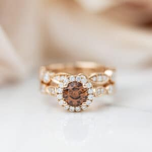 Peach tourmaline engagement ring with diamond halo and a scalloped diamond band