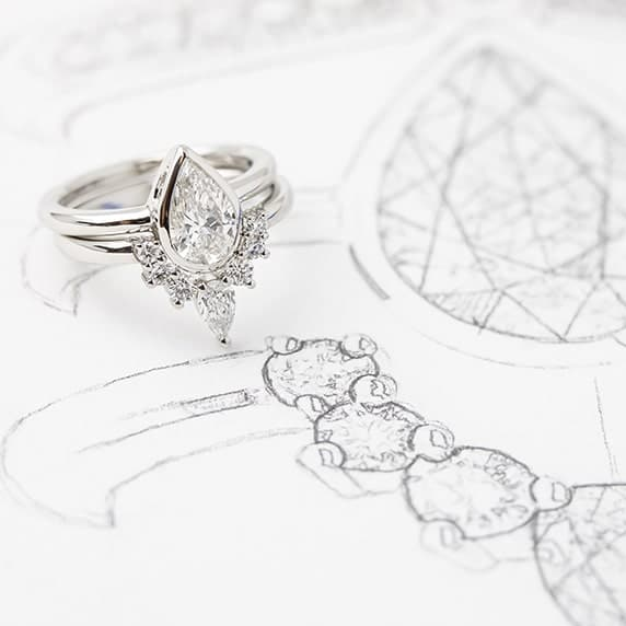Custom made wedding ring custom fitted to engagement ring resting on jewellery design sketches.