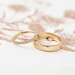 Rose gold handmade wedding rings with diamonds and milgrain detail, made by clients in a wedding ring experience.
