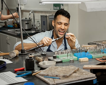 Client learning to make a wedding ring for his future wife in the make your own wedding ring experience at Larsen.