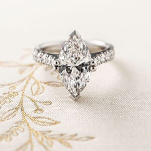Marquise diamond engagement ring with diamonds adorning the shoulders.