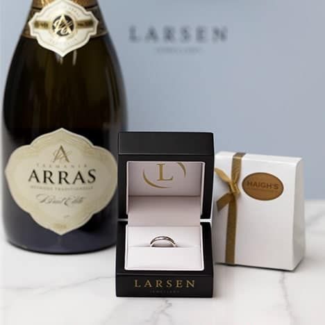 A finished Larsen jewellery proposal ring with box, ready to collect with a bottle of champagne