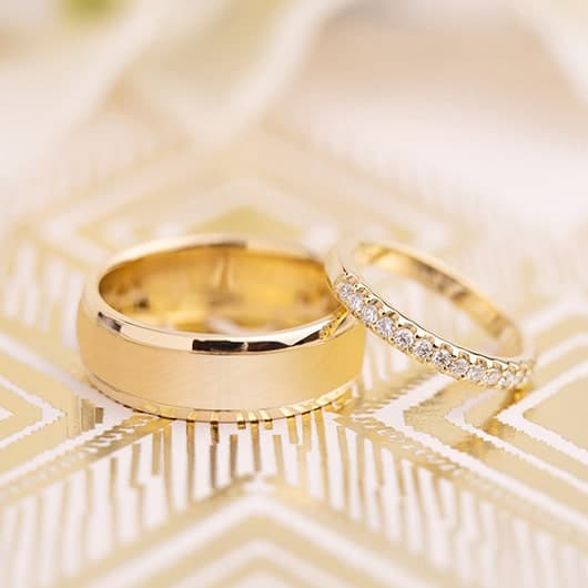 Men's Yellow gold brushed metal wedding band with women's diamond and yellow gold wedding ring