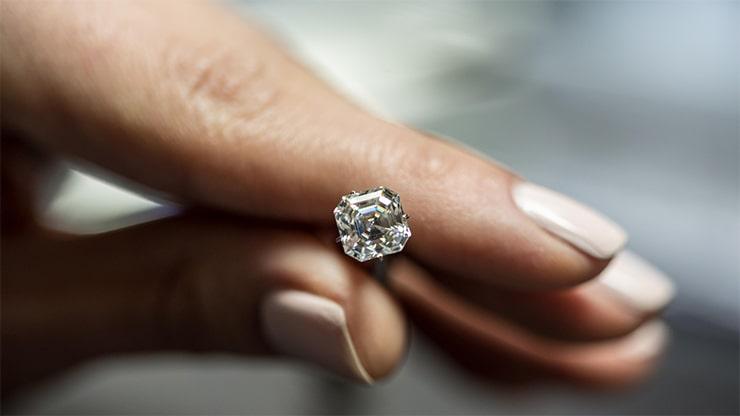 A woman holding an asscher cut diamond for a custom made engagement ring