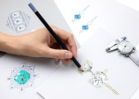 A jewellery designer sketches a pair of diamond and gold earrings