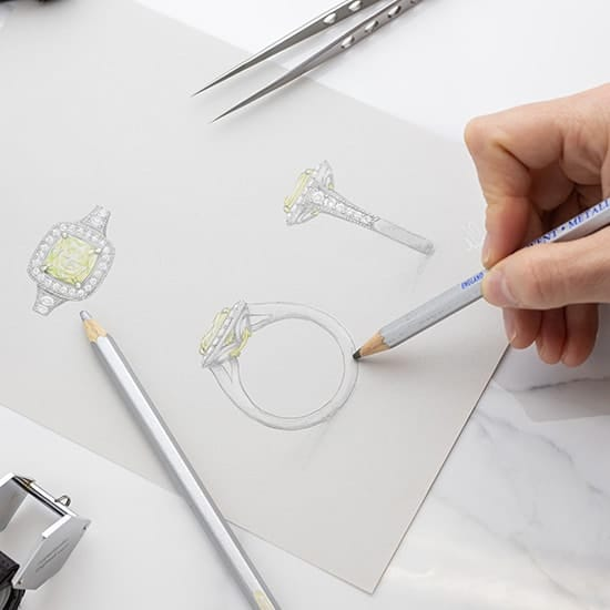 Jeweller sketches a bespoke engagement ring with a vivid yellow diamond in white gold with a halo.