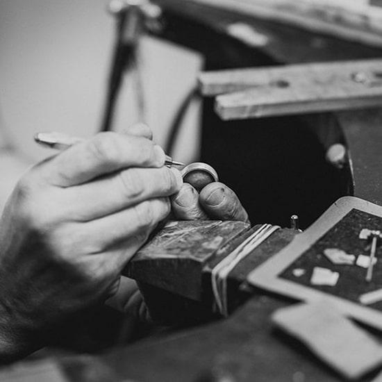 Jeweller handmaking a white gold custom wedding ring in a jewellery studio