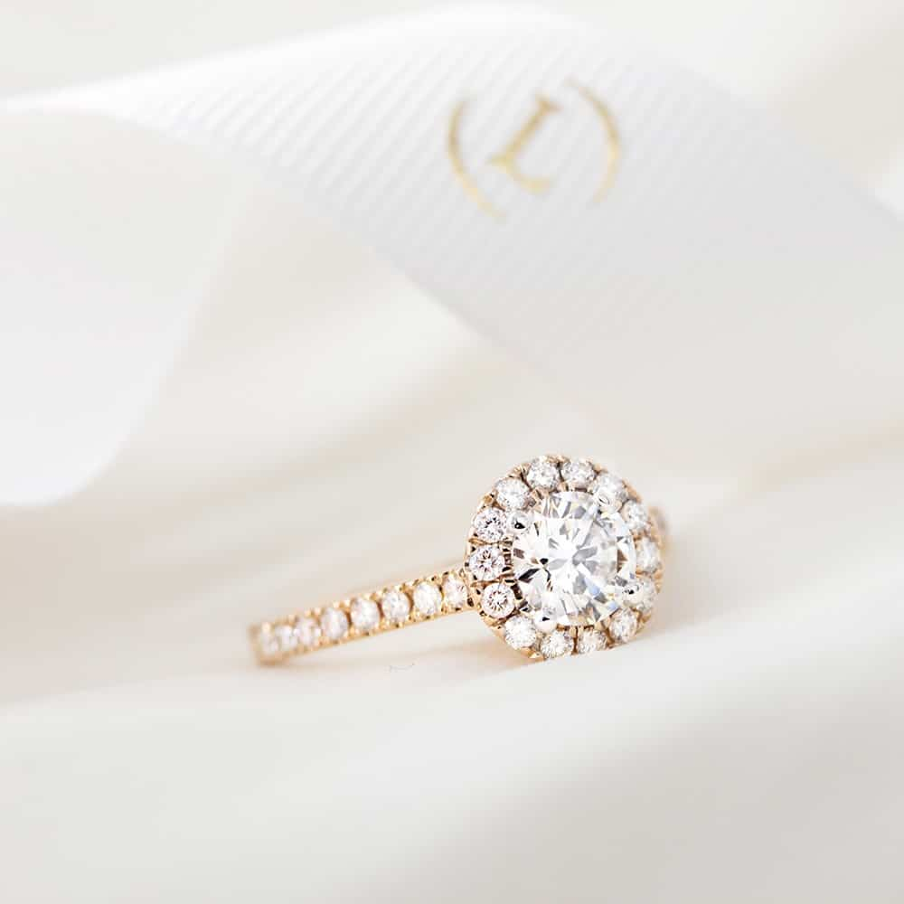 A rose gold diamond halo ring with a diamond microclaw band