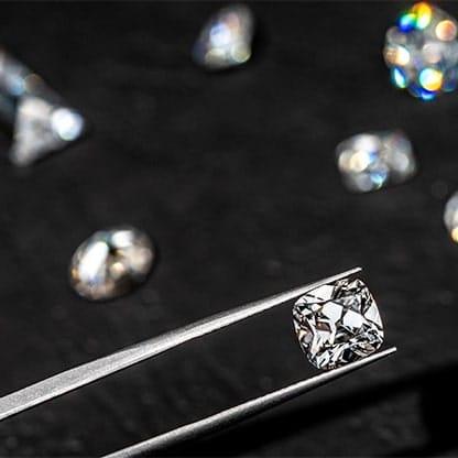 Cushion cut diamond in tweezers