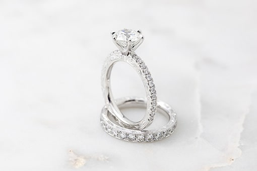 A white gold engraved diamond eternity ring and engagement ring made by Larsen Jewellery